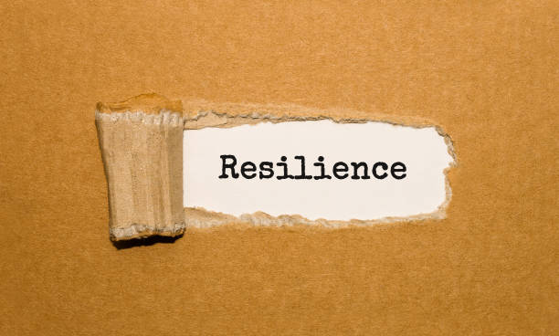 the text resilience appearing behind torn brown paper - endurance stock pictures, royalty-free photos & images