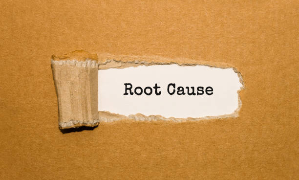 The text Root Cause appearing behind torn brown paper stock photo