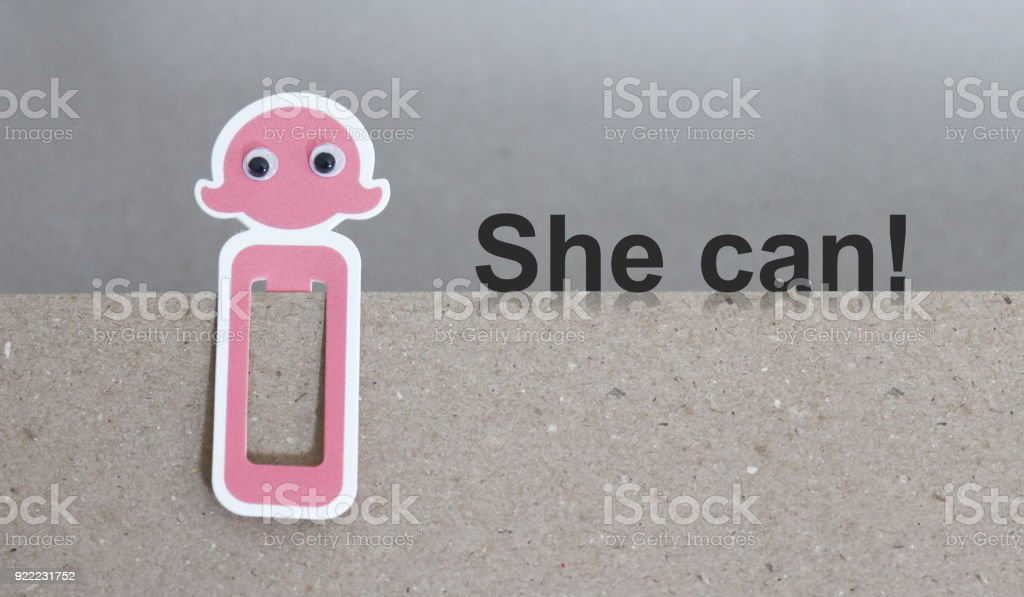 The text She can with a pink female-shaped bookmark. stock photo