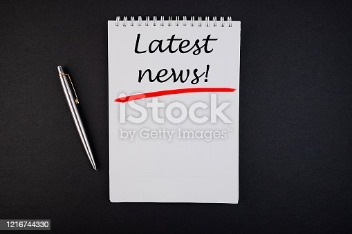 1132886484 istock photo The text, the inscription, the phrase Latest news is written in a notebook that lies on a dark table with a pen. Business concept. 1216744330