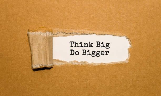 der text denken groß tun größer erscheint hinter zerrissenes papier braun - bedeutungsvolle zitate stock-fotos und bilder