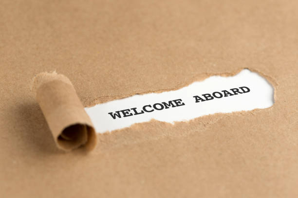 The text WELCOME ABOARD appearing behind torn brown paper The text WELCOME ABOARD appearing behind torn brown paper aboard stock pictures, royalty-free photos & images