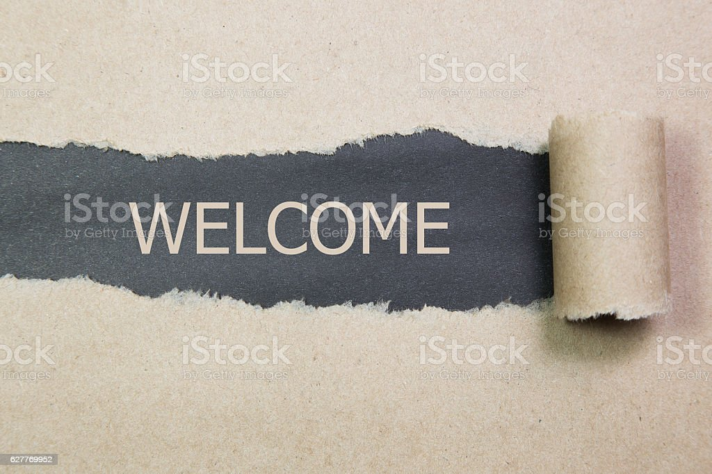 The text WELCOME behind torn brown paper stock photo