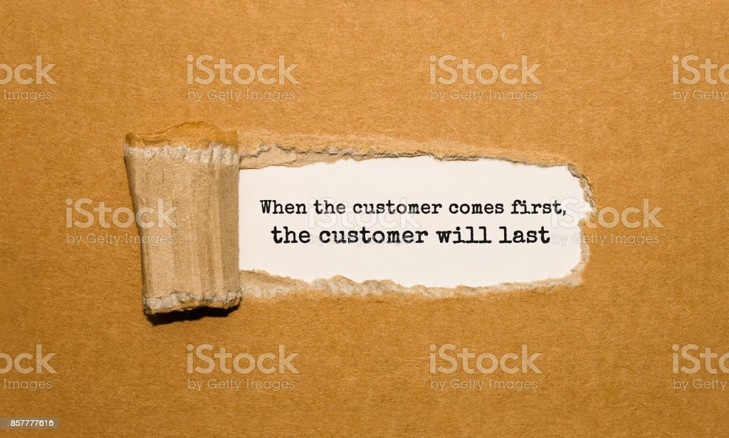 The text When the customer comes first the customer will last appearing behind torn brown paper stock photo