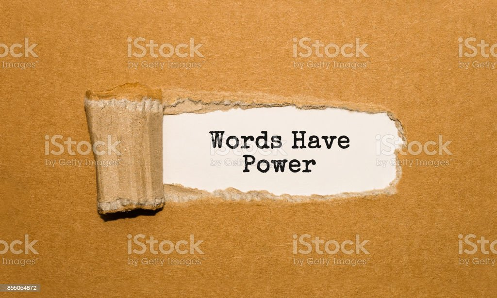 The text Words Have Power appearing behind torn brown paper stock photo
