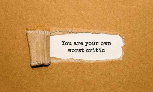 The text You are your own worst critic appearing behind torn brown paper The text You are your own worst critic appearing behind torn brown paper critic stock pictures, royalty-free photos & images