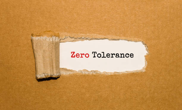 The text Zero Tolerance appearing behind torn brown paper The text Zero Tolerance appearing behind torn brown paper prettige verrassingen stock pictures, royalty-free photos & images