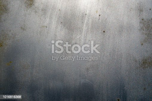 The texture of a silvery light shiny scratched aluminum globule of iron with rusty spots interspersed. The background.