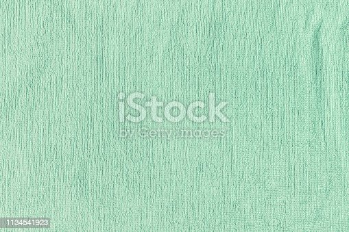 istock The texture of a terry towel. Green neutral background for layouts. 1134541923
