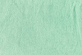 The texture of a terry towel. Green neutral background for layouts.