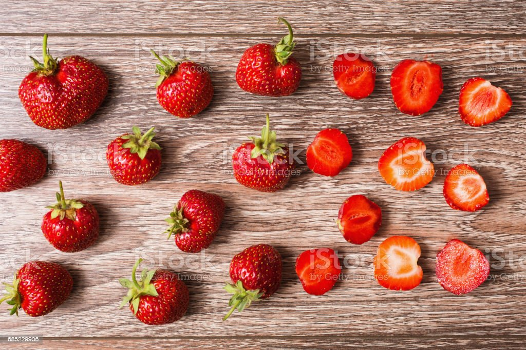 The texture of a whole and cut red ripe strawberries on wooden background. Summer ripe berries. foto de stock royalty-free