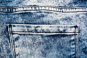 The texture of blue frayed jeans with a pocket  .Denim background