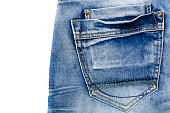 The texture of blue frayed jeans with a pocket on the isolate .Denim background