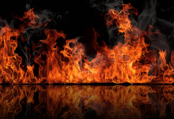 The texture of fire on a black background is reflected in a glossy table. stock photo