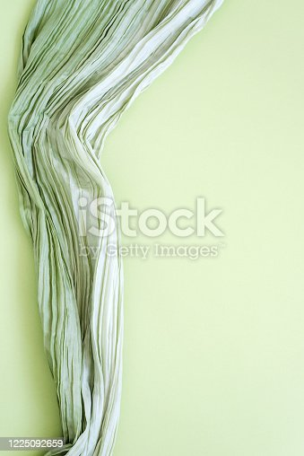 The texture of the background picture the mint green corrugated fabric with parallel or diagonal folds on textured paper. Blank for design, backdrop, concept of nature, springtime, fresh greenery.