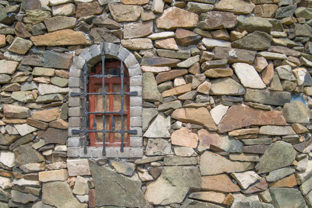 The texture of the castle wall with a window of stones stock photo