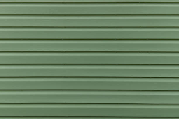 The texture of the green board of the exterior of the house siding panel. Parallel abstract stripes line stock photo