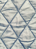 The texture of the quilted material. Quilted Background.
