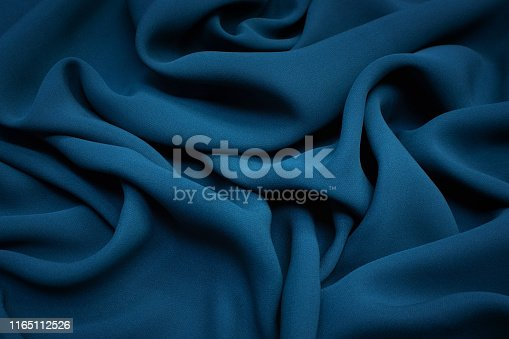 The texture of the silk fabric is the color of dark sea wave. Background, pattern.