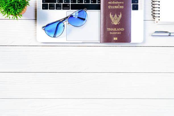 泰國人民工作者和員工辦公桌有旅行夢想和準備旅行和旅行在世界各地與筆記本電腦和泰國護照在白色木桌從平躺頂部視圖。圖像檔