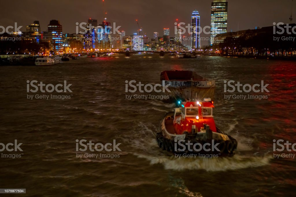The Thames at night with the West End skyline in the background and a tugboat pulling a large empty barge. stock photo