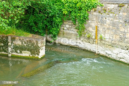 The wall of Oxford Gaol with a heron in the river underneath.