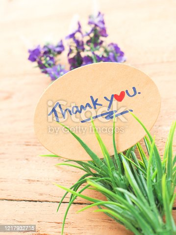 istock The thank you message is handwritten on a brown oval paper decorated with purple flowers and green leaves 1217932715