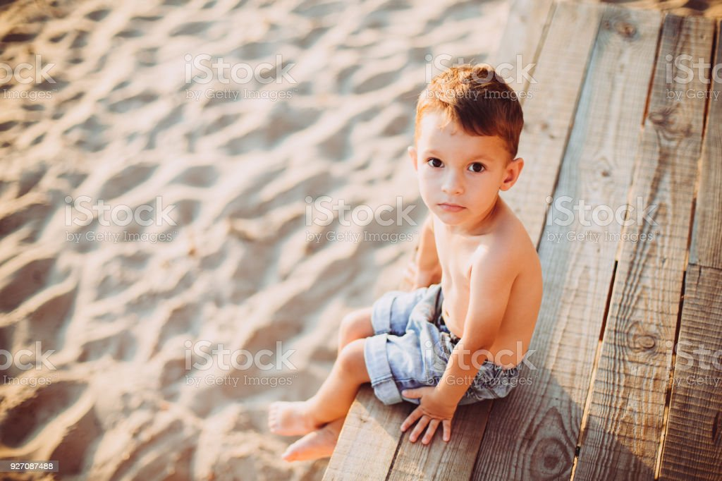 The theme is a child and summer beach vacation. A small Caucasian boy sits sideways on a wooden pier and looks at the camera on a sandy beach and a pond, a river. With bare legs in blue denim shorts stock photo