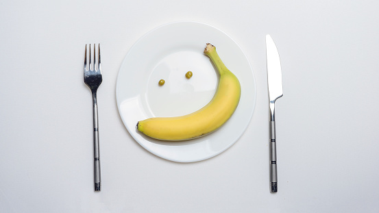 The theme of healthy eating: a banana and peas in the form of a smile on a plate, next to a knife and fork on a white table.