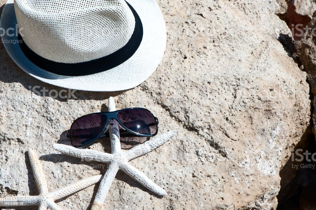 The theme of the beach, recreation, vacation. Straw hat, glasses and starfish stock photo