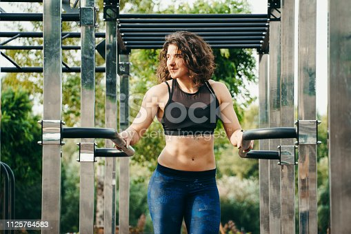 The theme women sports and health. Beautiful   caucasian woman with curly long hair posing on outdoor sports ground holding horizontal bar with tattoo on stomach in sports top and tight pants.