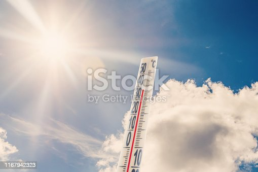 The thermometer against the blue sky and the sun shows the high temperature