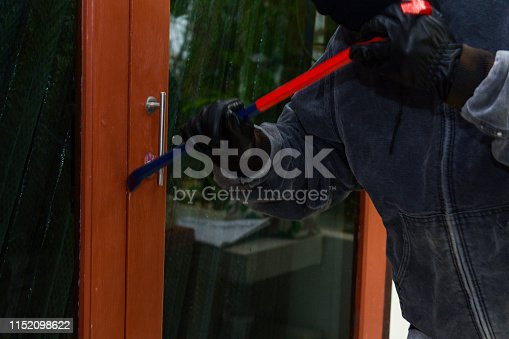 istock The thief is wielding the door. In order to steal property in the house 1152098622