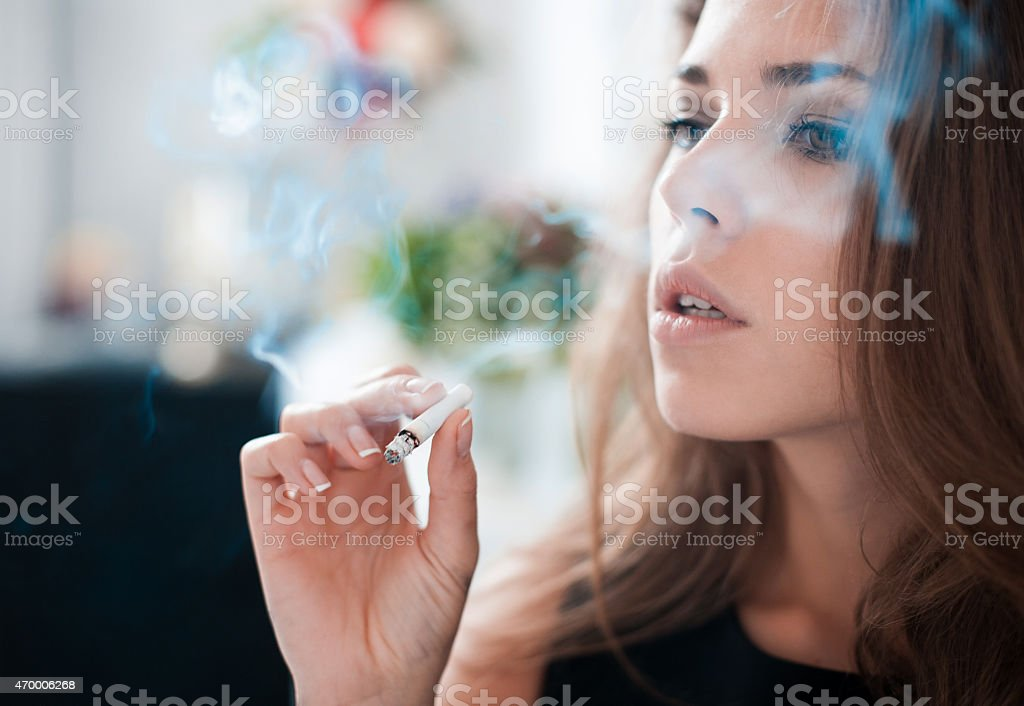 The thoughtful woman smokes a cigarette stock photo