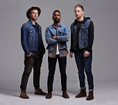 Full length portrait of three fashionable young men standing in studio