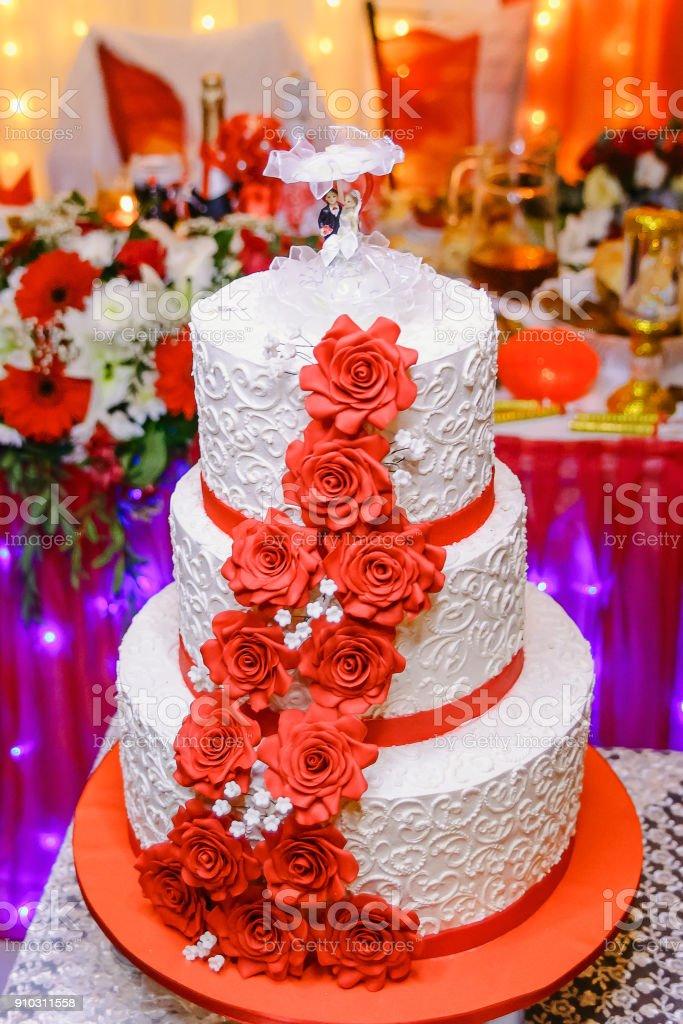 The Threestorey White Wedding Cake With Red Flowers Stock Photo