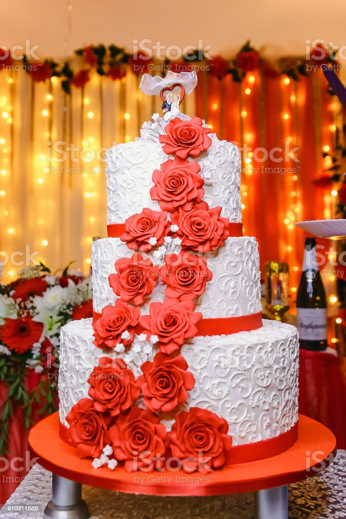 The Threestorey White Wedding Cake With Red Flowers Stock Photo