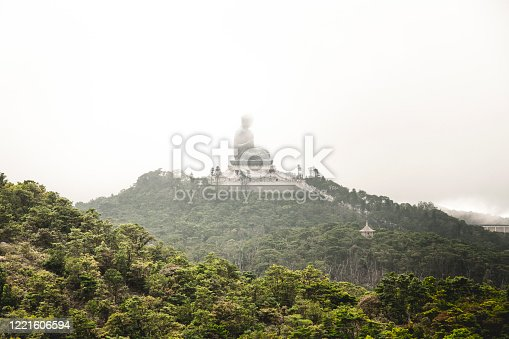 The Tian Tan Buddha on the mountain in Ngong Ping, Hong Kong in a cloudy day.