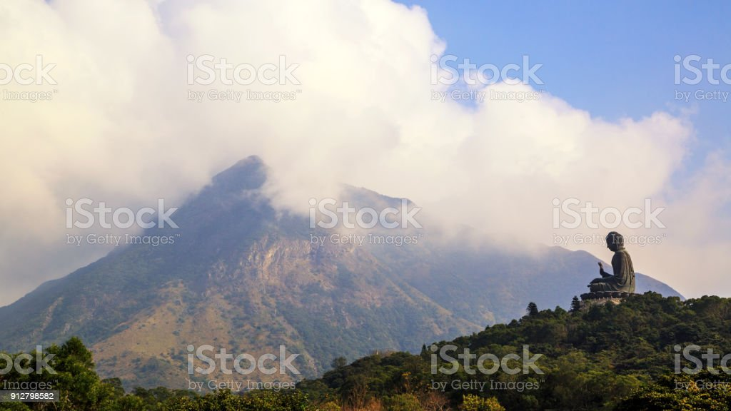 The Tian Tan Famous Big Buddha Statue Of Ngong Ping Village with hill top on background stock photo
