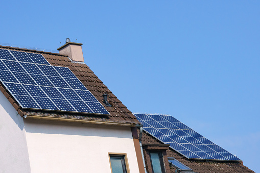 The tiled roof of the house with a chimney is covered with solar panels. Blue sky.