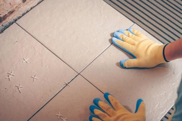 der fliesenleger bellt und legt seine hände in gelben handschuhen eine quadratische kachel auf dem boden - keramik fliesen handwerk stock-fotos und bilder