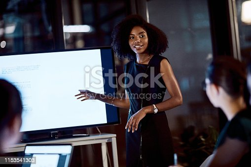 Shot of a young businesswoman delivering a presentation during a late night meeting at work