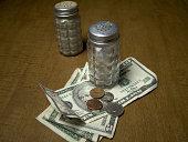 Salt and pepper shaker on a wood table.  Salt shaker on money.