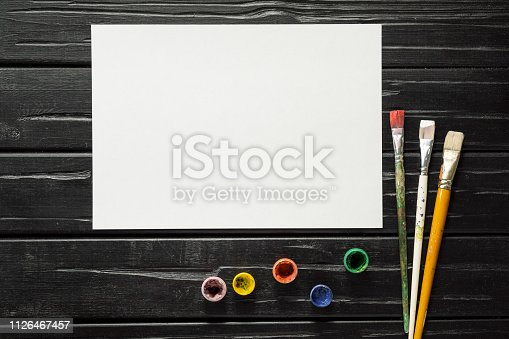629775804 istock photo The tools of the artist, brushes, paints and canvas are not dark wooden background. 1126467457