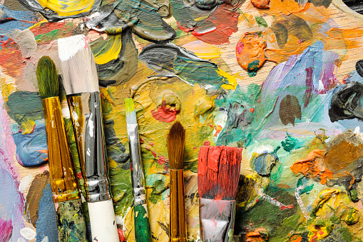 istock The tools of the artist, brushes, paints and palette not dark wooden background. 1126467471