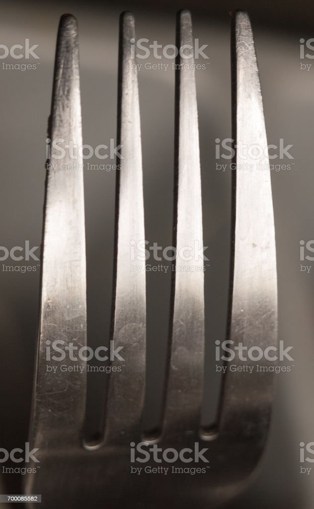 the top four prongs of a metal fork up close shining and reflecting in studio stock photo