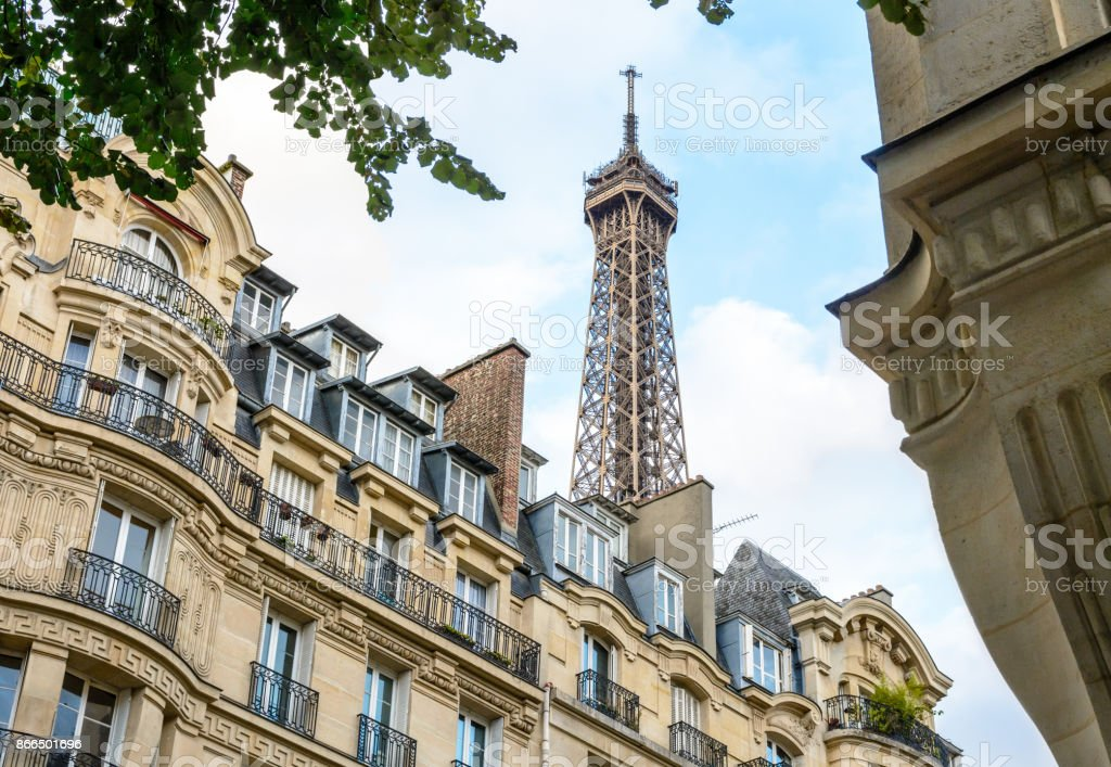 The top of the Eiffel Tower seen from down the street with foliage and typical residential buildings in the foreground stock photo