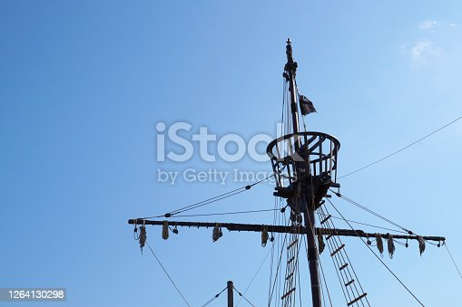 the top of the mast of an old ship against the backdrop of a sunny sky, copy space