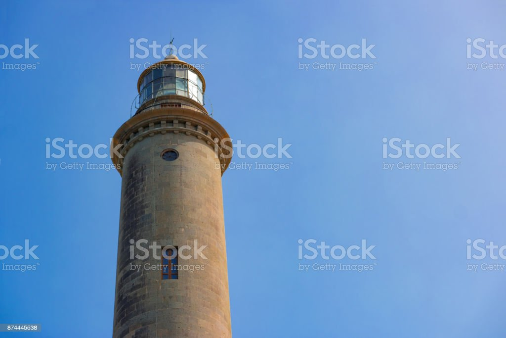 The top of the old Maspalomas Lighthouse against a clear blue sky with copyspace stock photo