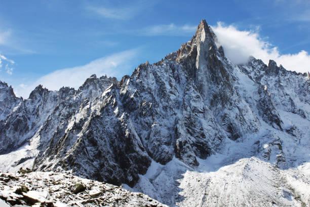 La cima de la montaña cubierta de nieve entre las nubes. - foto de stock